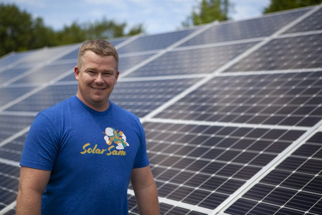 Solar Sam Owner, Ches Headshot, with a Solar Panel Array Installation Behind Him. Servicing both Missouri Illinois Solar Panel Needs